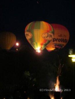 Baumfackel vor Heißluftballons bei Feuer-Performance